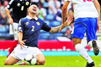 Scotland full-back Alan Hutton is left in agony after being caught by Filip Duricic Photograph: Stewart Attwood