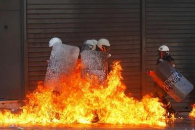 ON THE DEFENSIVE: Riot police find themselves surrounded by flames during violent protests against austerity measures in Greece. Picture: Reuters