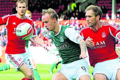 Hibernian striker Leigh Griffiths shields the ball from Aberdeen's Russell Anderson at Pittodrie Stadium			   Photograph: SNS
