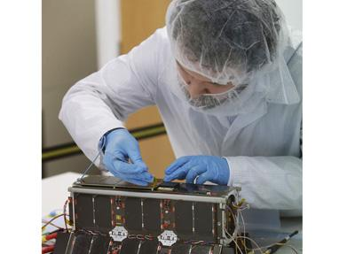 Kevin Worrall, Senior Engineer at Clyde Space, with the UKube-1 satellite, Scotland's first satellite, at Clyde Space in Glasgow.