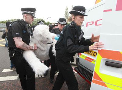 A demonstrator dressed as a polar bear is taken away by police